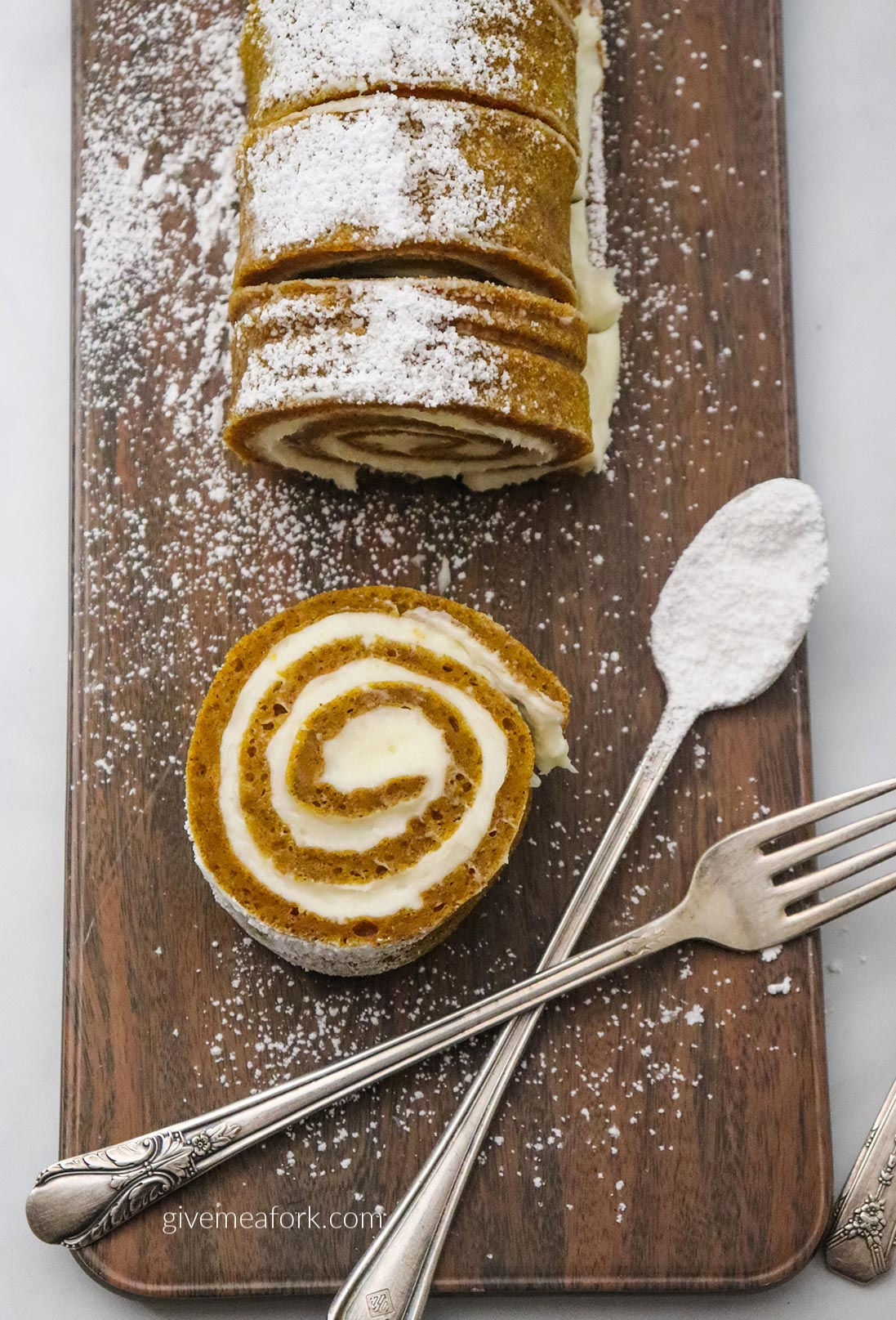 pumpkin roll on a wooden board with a fork and spoon