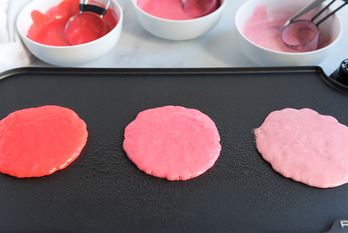 3 pink pancakes on a black electric griddle