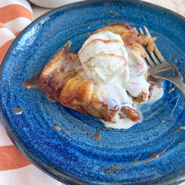 apple dumplings with vanilla ice cream, caramel syrup, and a fork on a blue plate with an orange towel on the side.