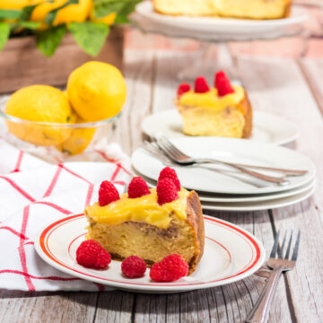 a slice of instant pot raspberry lemonade cheesecake on a white and red plate with a fork, towel, and lemons on the side.