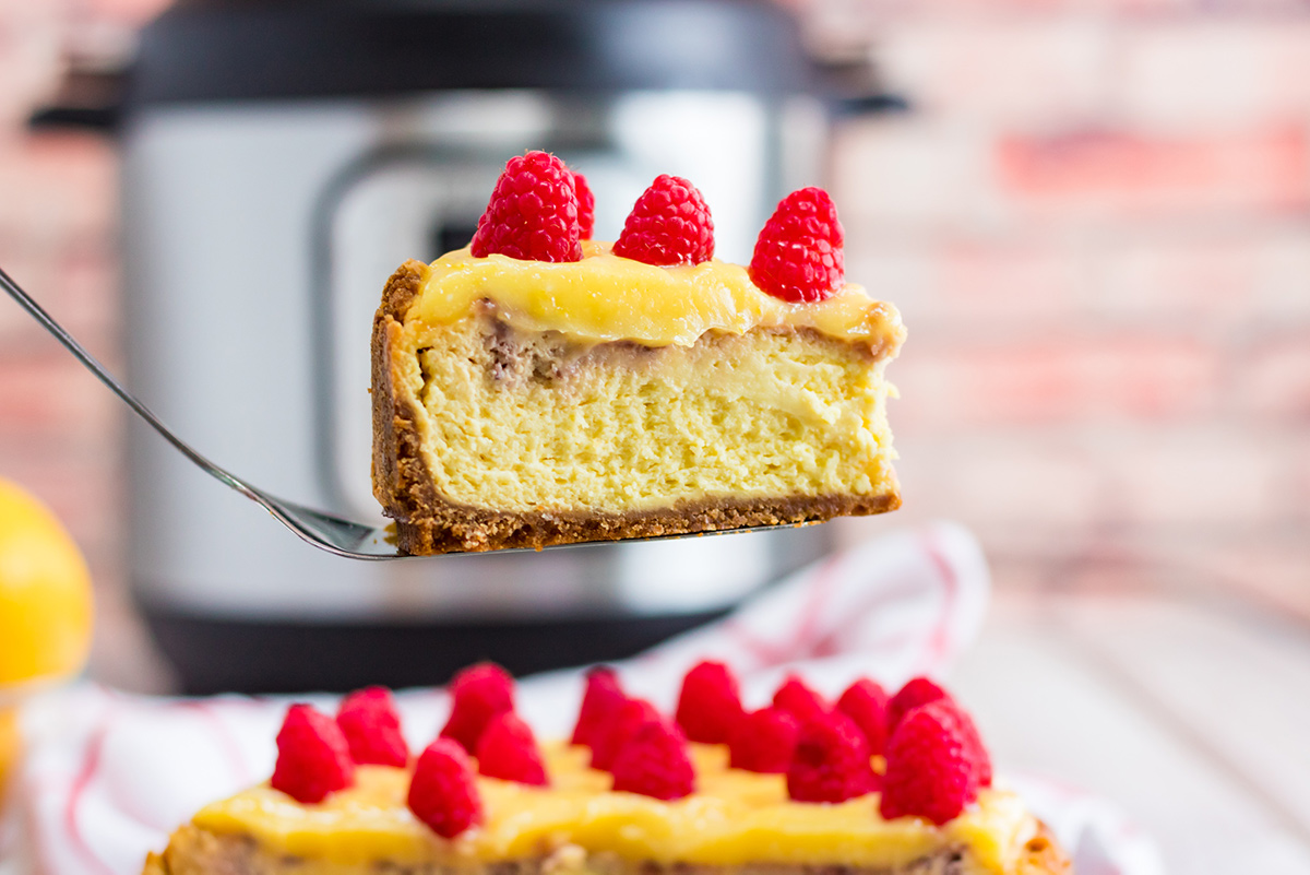 a slice of cheesecake with raspberries on top and an instant pot in the background.