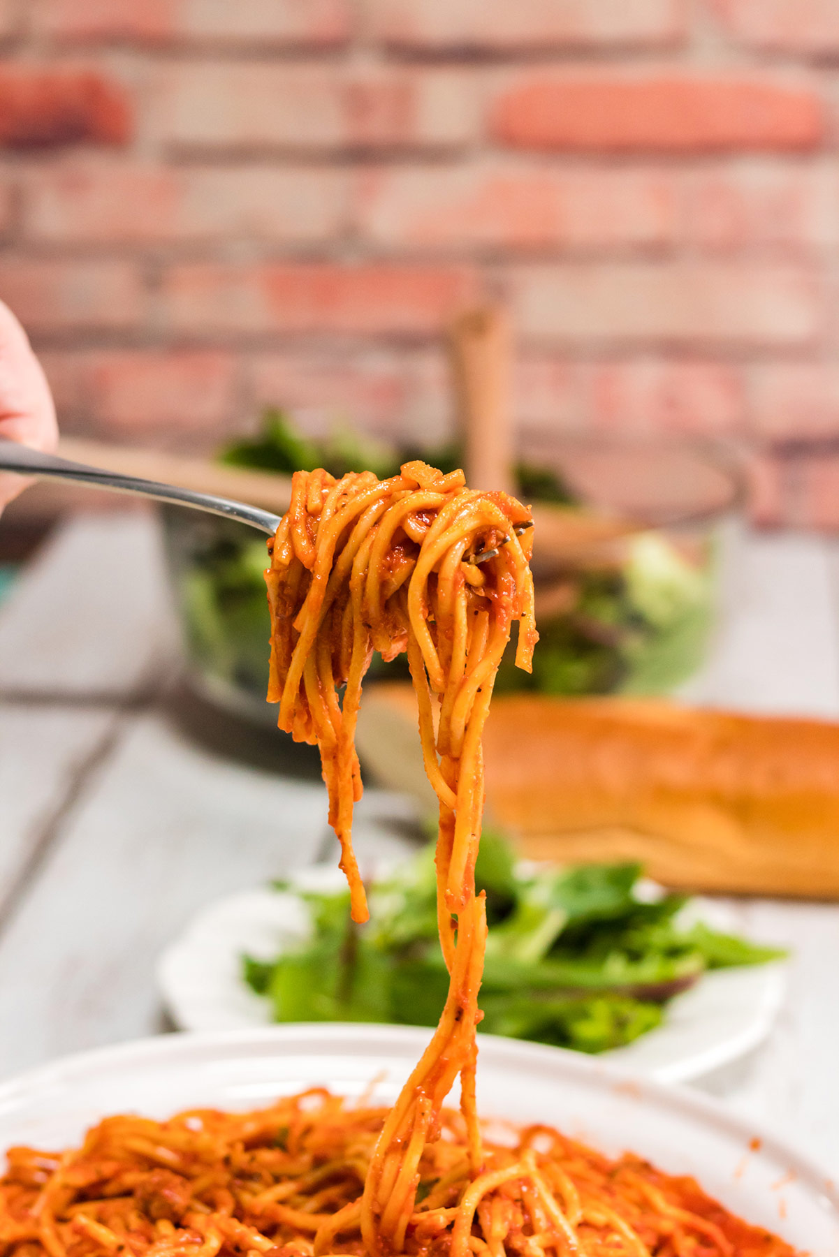a fork lifting spaghetti from a bowl. Fresh herbs and a red bricked wall in the background.
