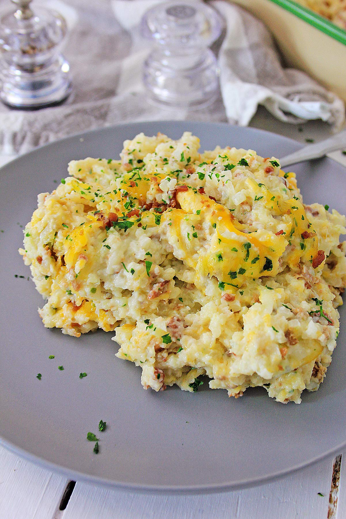 loaded cauliflower bake on a gray plate with salt shakers on the side and a green casserole in the background.