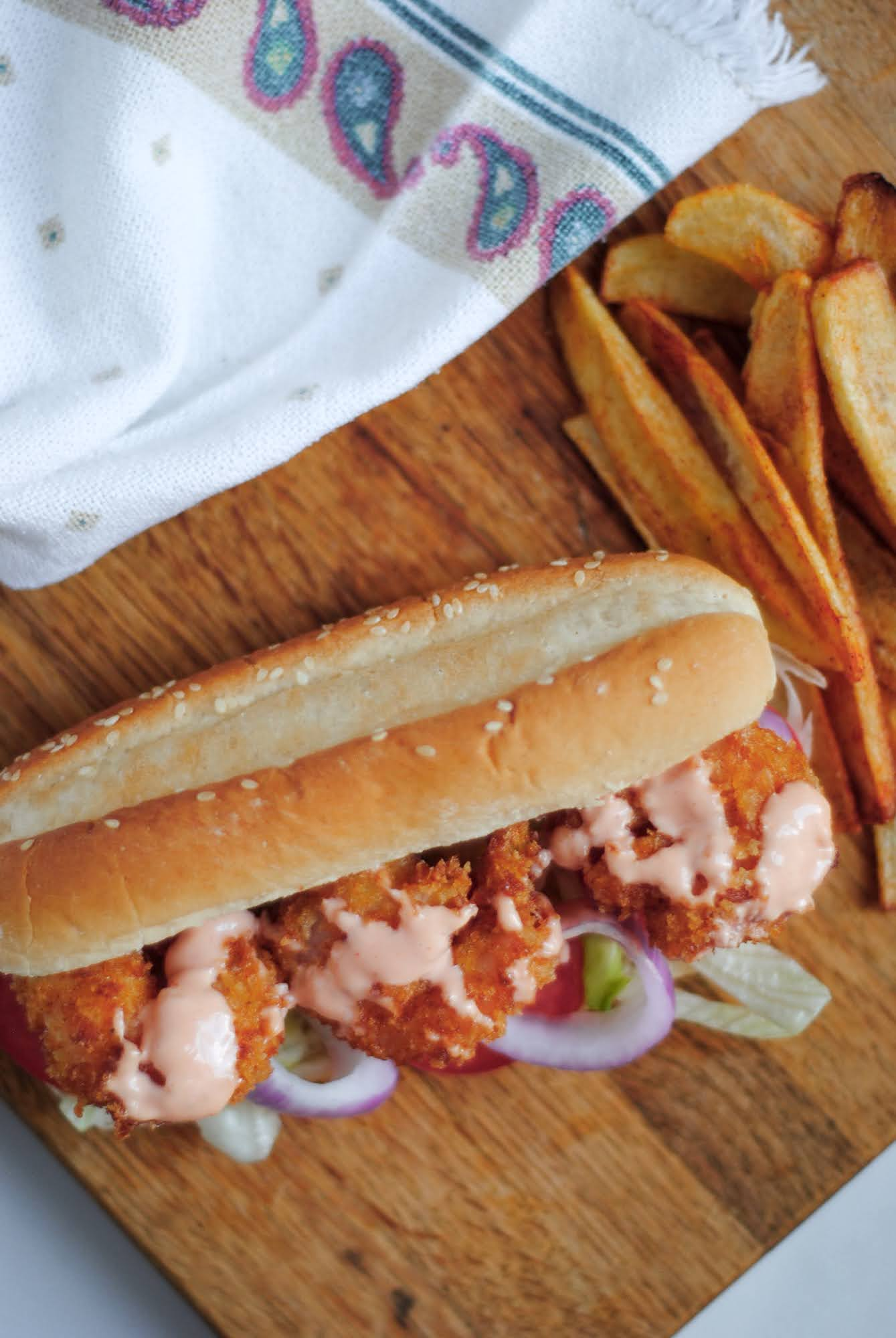 shrimp po'boy sandwich on a wooden board with french fries and a towel on the side.