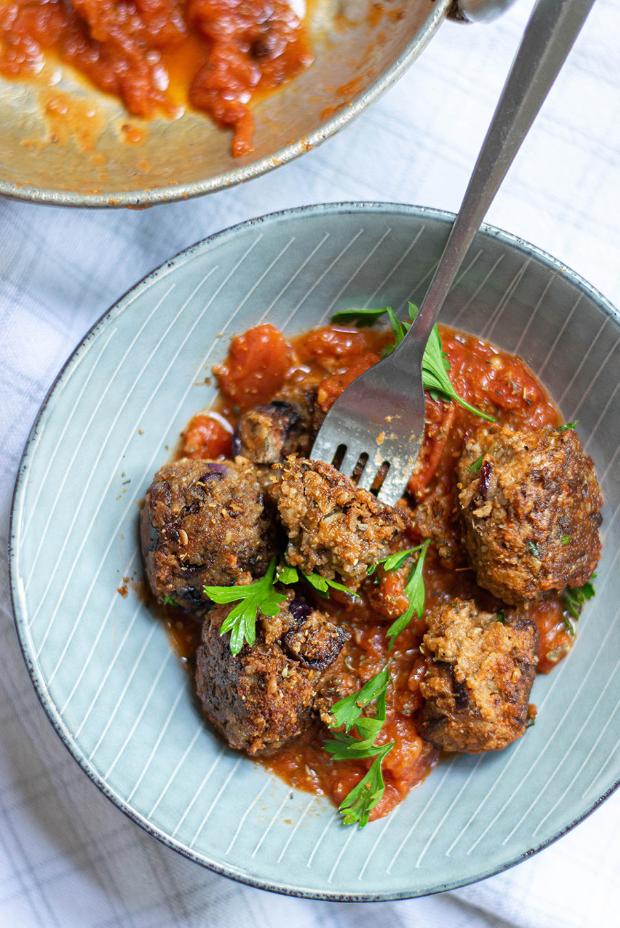 five lentil vegetarian meatballs with marinara sauce and parsley in a light blue bowl with a fork.