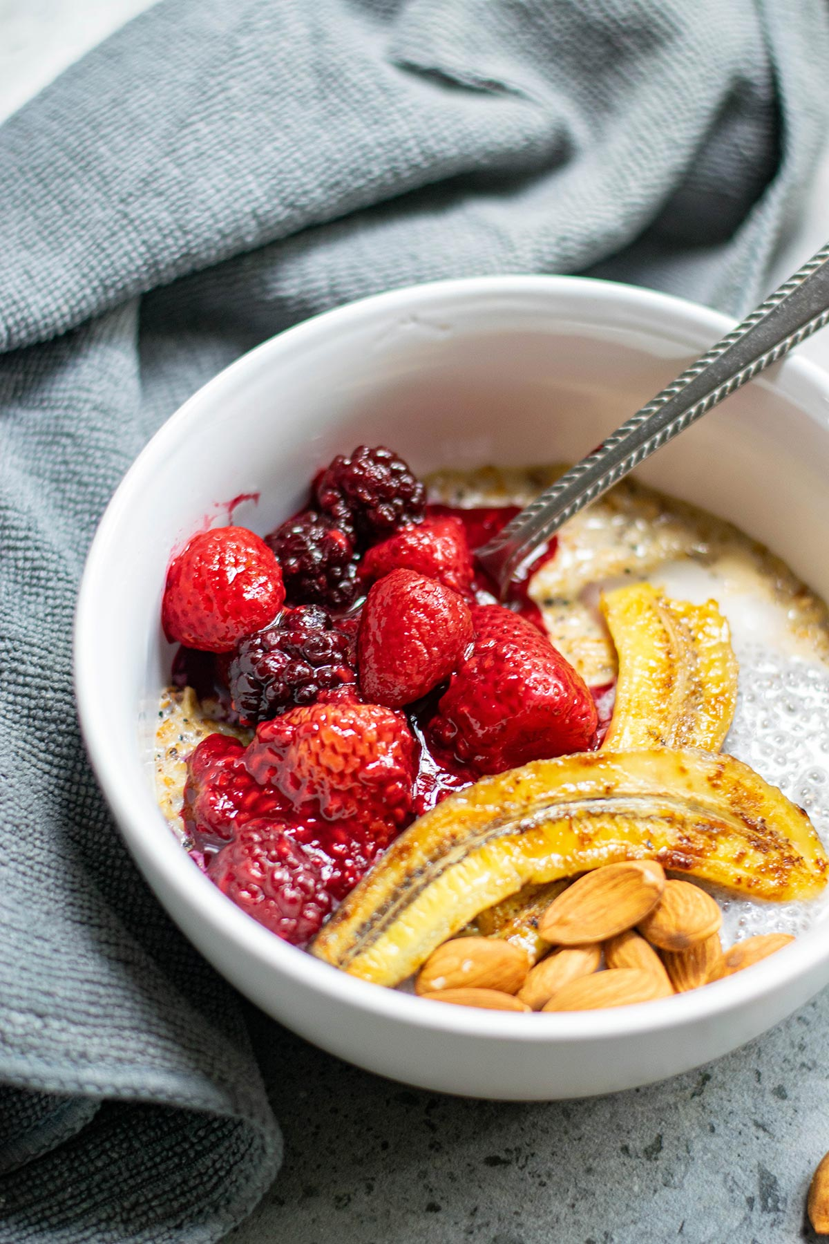 a white bowl with oats, berries, bananas, nuts, and a spoon. A blue towel on the side.