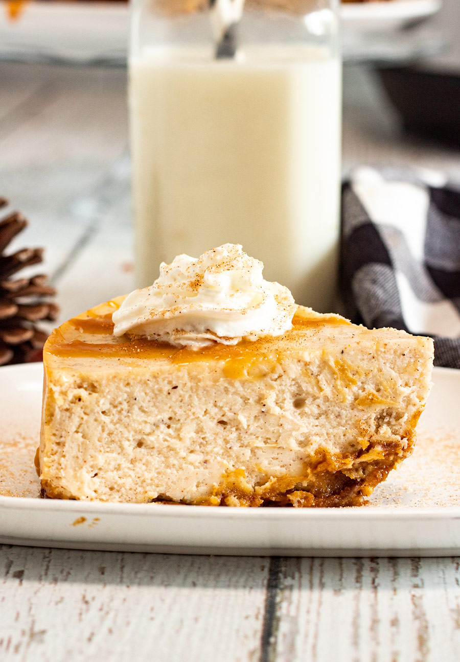 a slice of eggnog cheesecake with caramel and whipped cream on top and milk in the background.