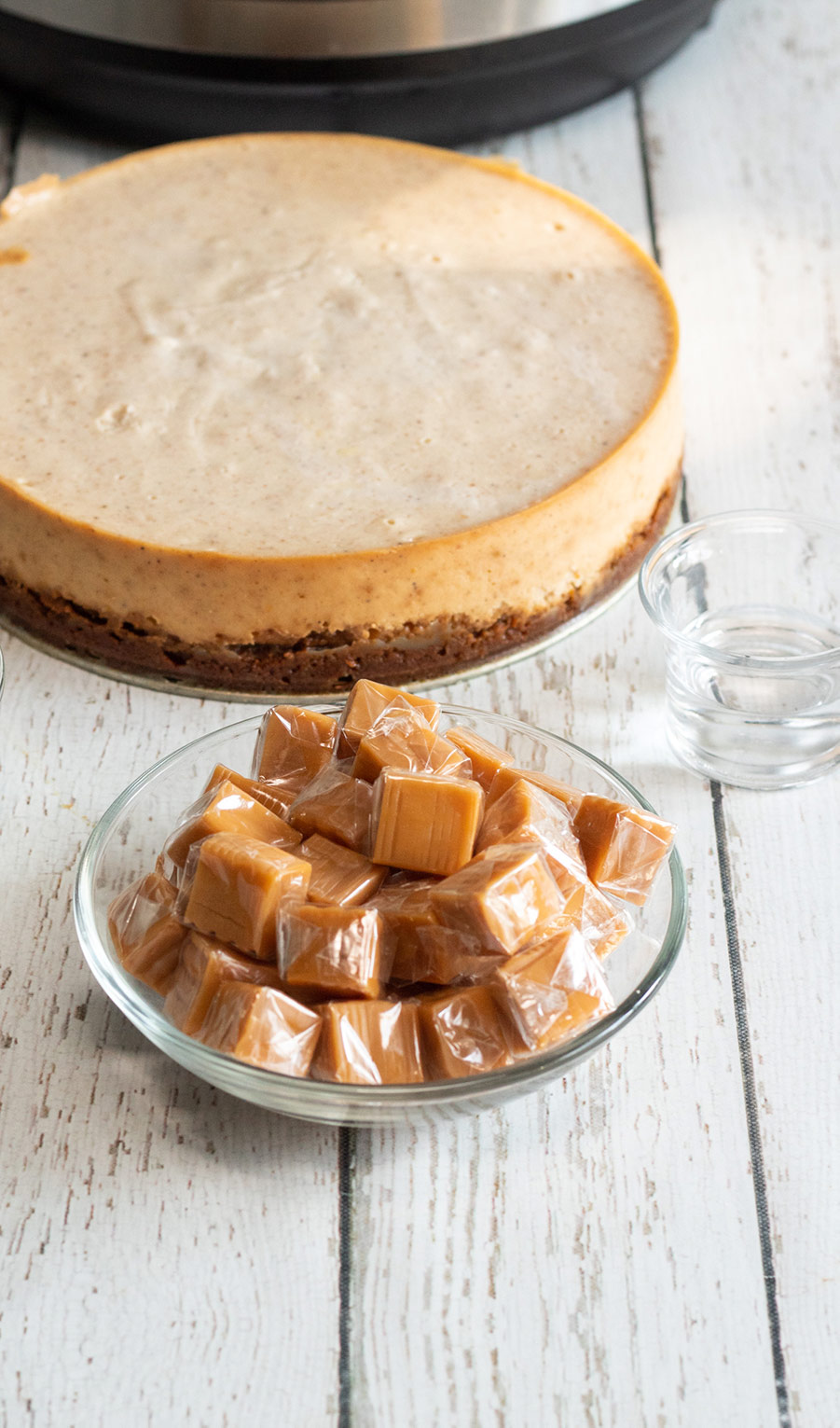 eggnog cheesecake in the background and a bowl of caramel candies up front.