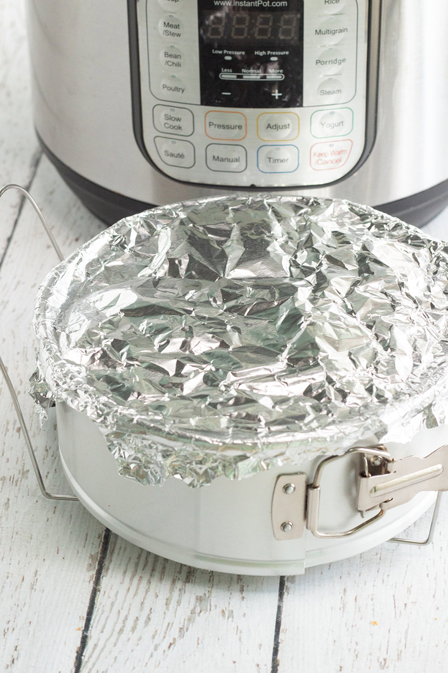 springform pan covered with aluminum foil and an instant pot in the background.