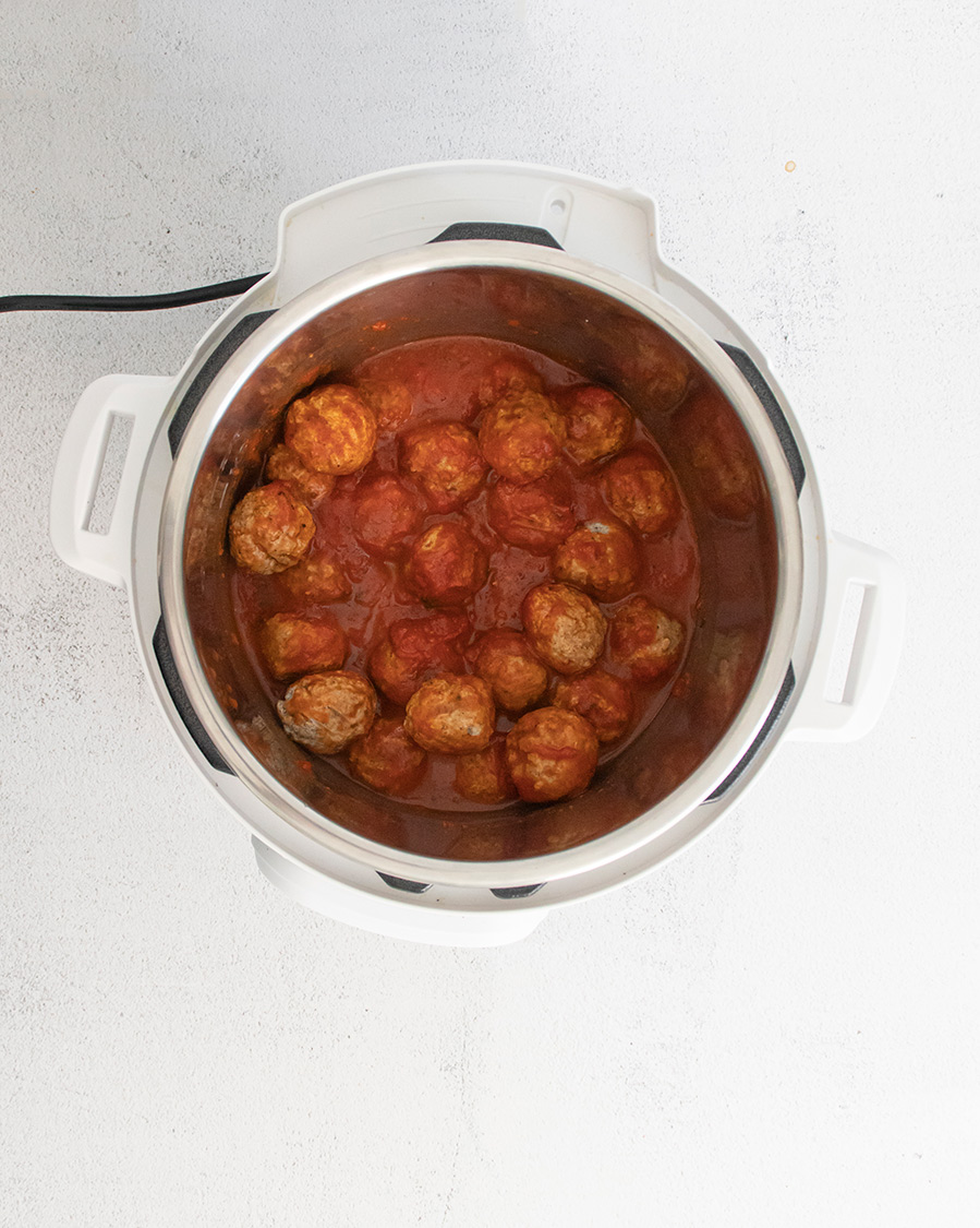 cooked meatballs with marinara sauce in a white instant pot.