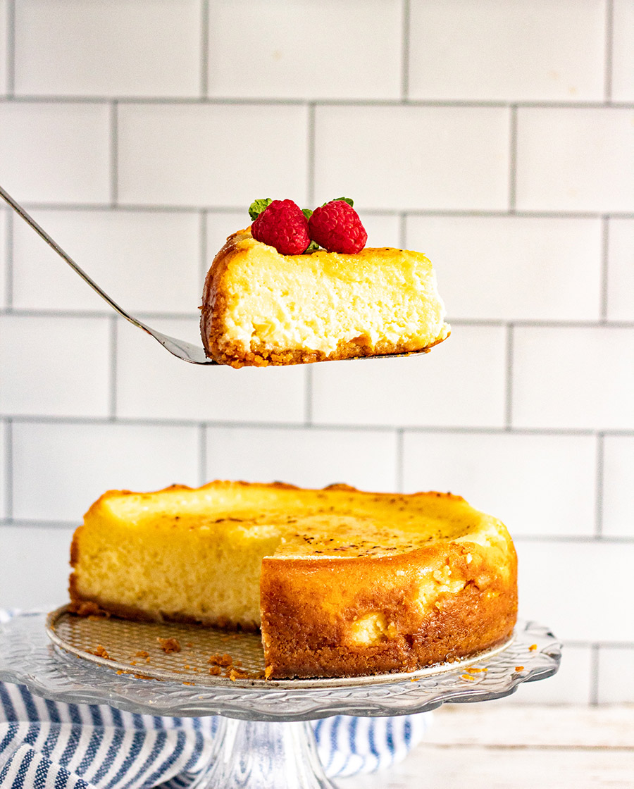 a spatula lifting a slice of cheesecake over an entire cake.