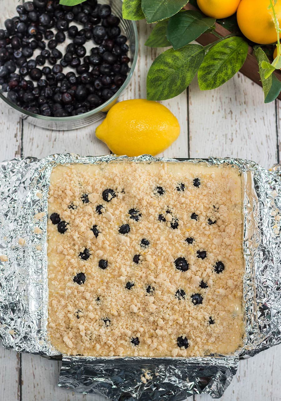 cake in a baking dish with a lemon and blueberries on the side.
