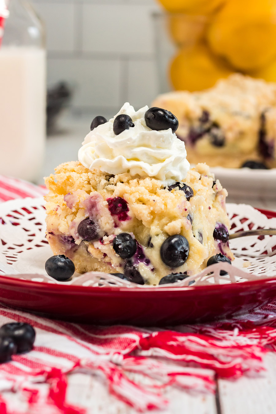 a slice of blueberry cake with whipped cream on a plate.