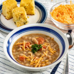 bean and bacon soup in a bowl with corn bread and cheese in the background.