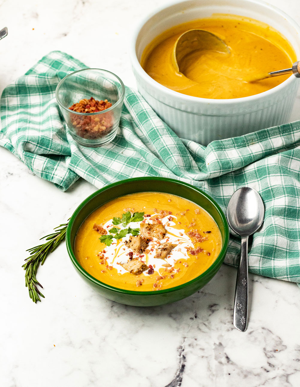 butternut squash soup in a green bowl with cream and bacon on top.