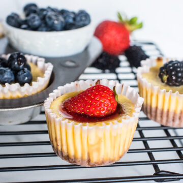mini cheesecakes with strawberries, blueberries, and blackberries on top.