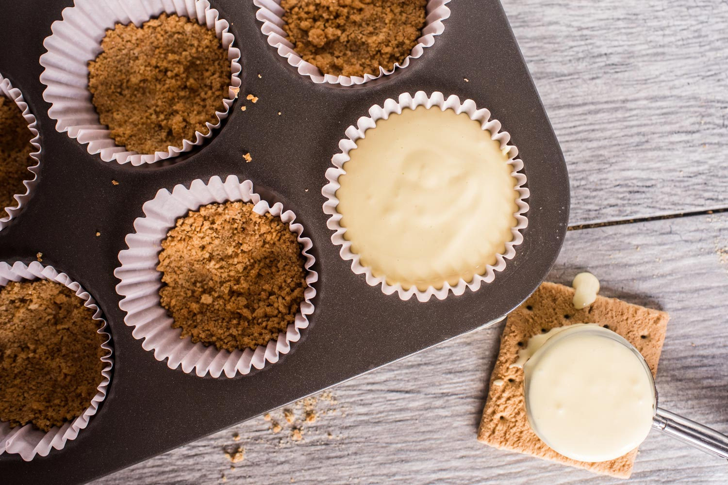 cupcake tin with cupcake liners filled with graham cracker crust and cheesecake filling.