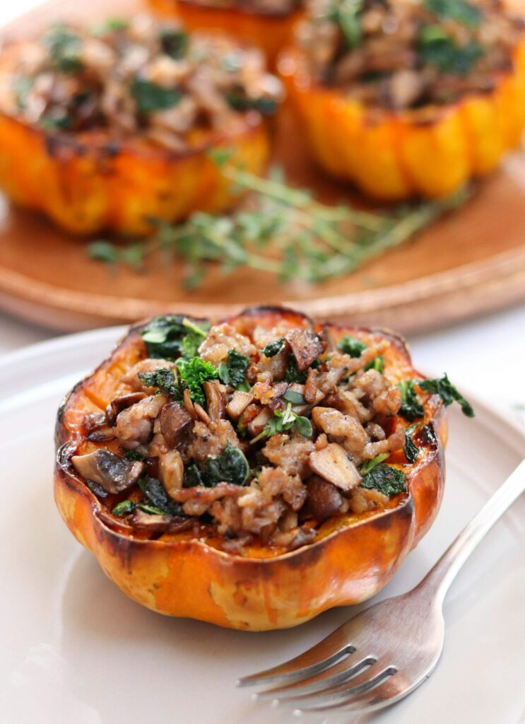 acorn squash filled with kale and sausage on a white plate with a fork.